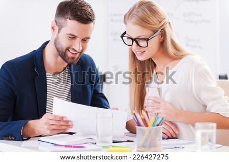 Discussing contract together. Two confident business people in smart casual wear sitting together at the table and discussing something while looking at the document - stock photo