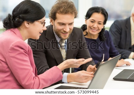 Discussing ideas. Mature businesswoman talking to her male colleague during business meeting showing something on the digital tablet discussion partnership co-working teamwork brainstorming concept