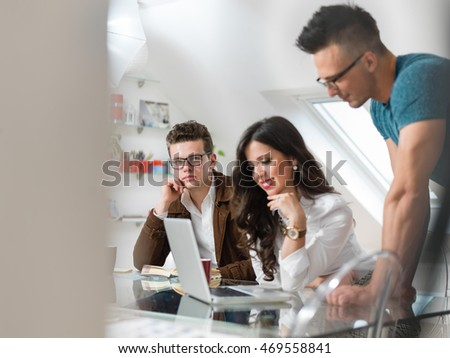 discussing market research with colleagues in a meeting. Team of young professionals having a meeting in conference room looking at documents.
