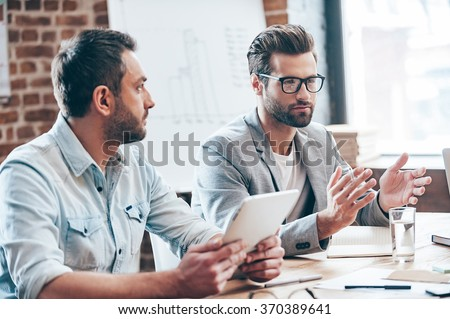 Discussing new business strategy. Young handsome man wearing glasses gesturing and discussing something while other young man holding touchpad and listening to him sitting at the office table - stock photo