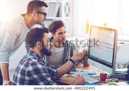 Discussing new project. Three young business people discussing something while looking at the computer monitor together  - stock photo