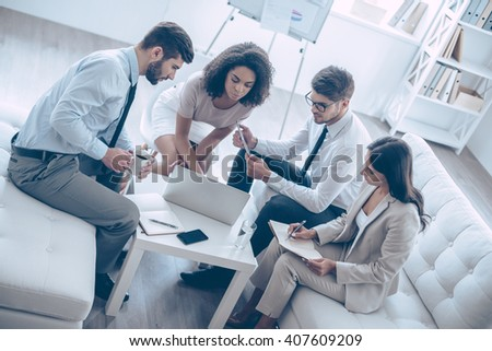 Discussing new project. Top view of group of four young people looking at laptop while sitting on the couch at office  - stock photo