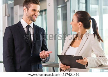 Discussing new project. Two cheerful business people discussing something and smiling  - stock photo