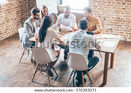 Discussing new strategy. Group of six young people discussing something while sitting at the table in office together - stock photo