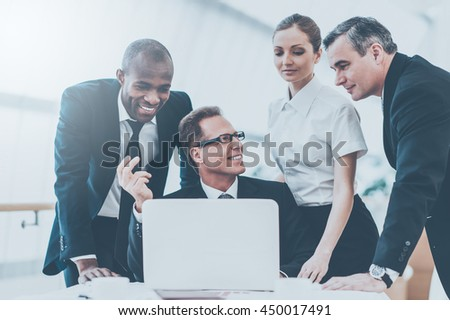Discussing some business issues. Business people in formalwear discussing something while man pointing a paper with a pen and smiling - stock photo