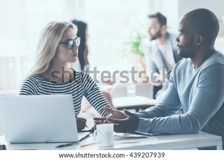 Discussing some business issues. Two young business people discussing something while sitting at the office desk together while their colleagues sitting in the background - stock photo