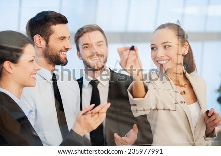 Discussing successful business project. Confident young businesswoman drawing a graph on glass and smiling while her colleagues standing near her  - stock photo