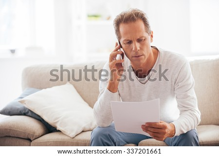 Discussing that document. Serious mature man holding paper and talking on the mobile phone while sitting on the couch at home - stock photo