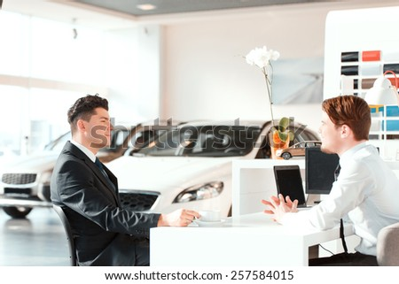Discussing the deal. Side view of a young handsome salesman speaking with his satisfied client in car dealership while sitting at the table and drinking coffee - stock photo