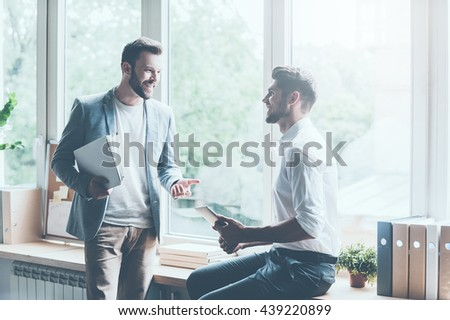 Discussing their successful project. Two young businessmen in smart casual wear talking and gesturing while leaning at the window sill in office  - stock photo