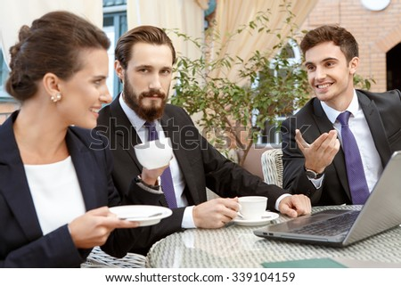 Discussing with co-workers. Businesspeople meeting in an outdoor restaurant  - stock photo
