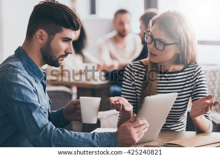 Discussing work. Young beautiful woman gesturing and looking at her coworker while sitting at the office table  - stock photo