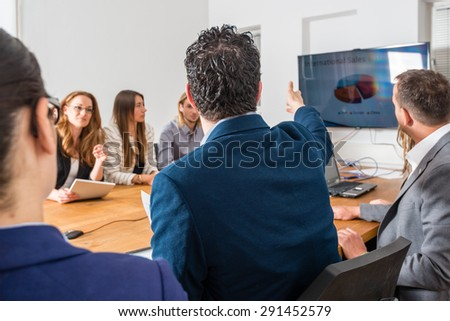 Discussion during a business meeting in a conference room - mixed caucasian team rather casual, ambiente might suggest a startup or an agency  - stock photo