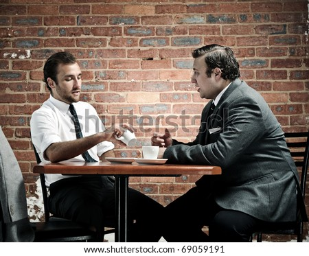 discussion in a coffee shop by two vintage businessmen - stock photo