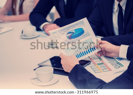 Discussion of business plan. Four smiling successful businessmen sitting at table in office while discussing their business doings. Young people talking in office - stock photo