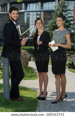 Discussion of project details. Three confident and motivated business partners are discussing future business forum. Both are wearing formal suits. Outdoor business concept - stock photo