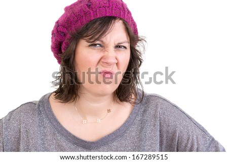 Disdainful woman in a purple knitted beanie screwing up her nose in disgust and dislike, head and shoulders isolated on white - stock photo