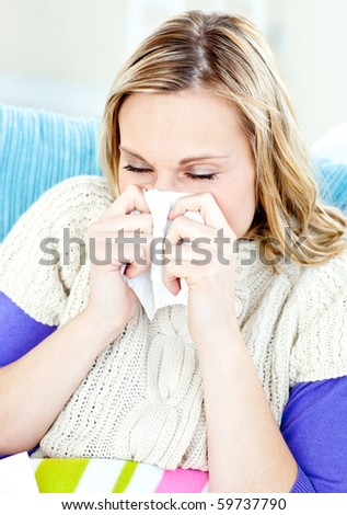 Diseased woman lying on a sofa with tissues and blowing against a white background - stock photo