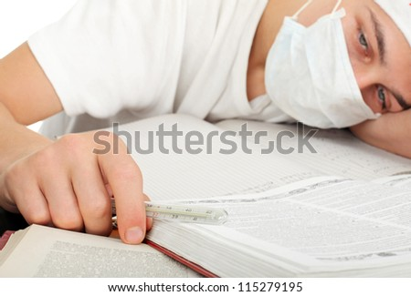 diseased young man in flu mask lying on the table closeup - stock photo