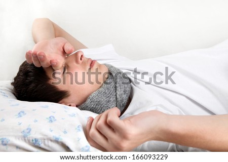 Diseased Young Man lying on the Bed and feels Headache