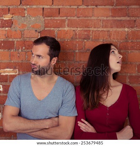 Disgruntled couple ignoring one another after an argument standing looking in opposite directions with folded arms - stock photo