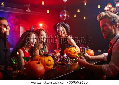 Disguised vampire serving drinks to witches at Halloween night - stock photo