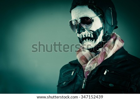 Disgusted aviator with face painted as human skull - stock photo