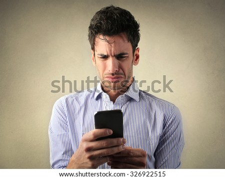 Disgusted man reading a text message - stock photo