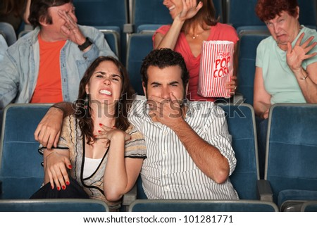 Disgusted people watch movie in a theater - stock photo