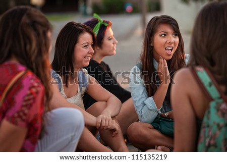 Disgusted teenage girl sitting on the ground talking with friends - stock photo