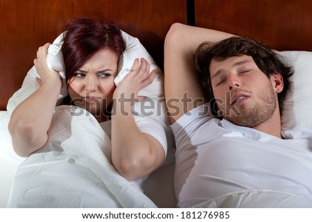 Disgusted wife and her sleeping husband in bed - stock photo