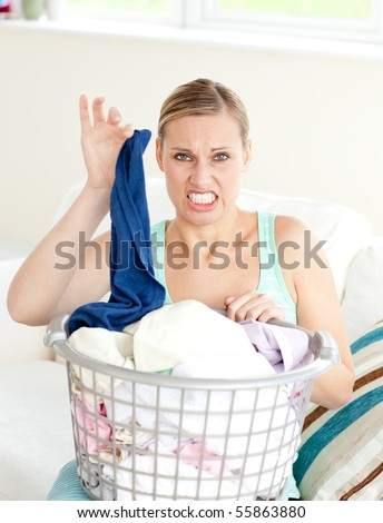 Disgusted woman doing her laundry at home - stock photo