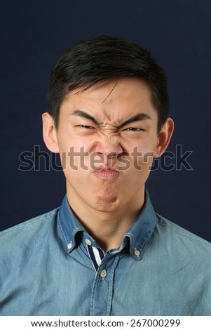 Disgusted young Asian man making face and looking at camera - stock photo