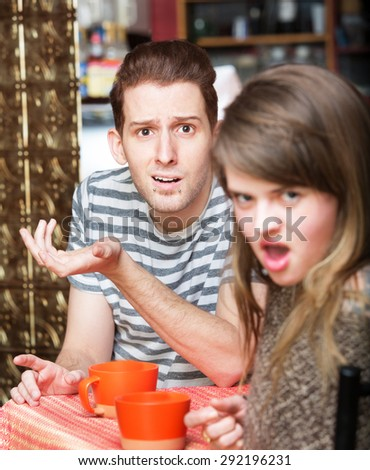 Disgusted young woman with frustrated man at cafe - stock photo