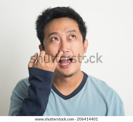 Disgusting Asian man picking nose with eyes looking up, on plain background - stock photo