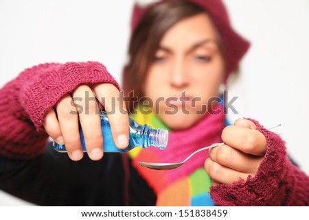 disgusting medicine being poured on a spoon by sick woman - selective focus on foreground - stock photo