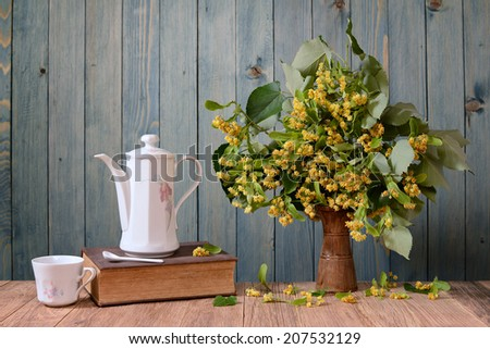 Dish for tea cups and flowers of linden in vase on the table - stock photo