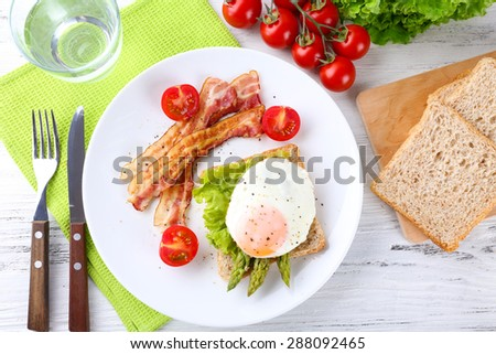 Dish of asparagus with bacon and egg in plate on table, top view - stock photo