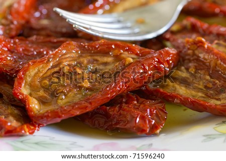 Dish of dried tomatoes in oil with a metal fork closeup