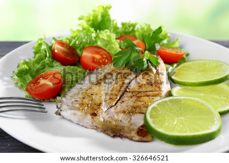 Dish of fish fillet with salad and lime on plate close up - stock photo