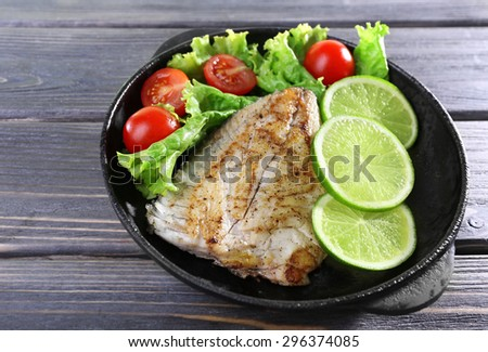 Dish of fish fillet with salad and lime on table close up - stock photo