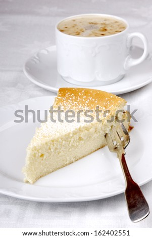 Dish of german cheesecake with a cup of cappuccino - stock photo