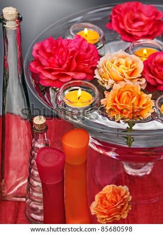 Dish of glass and water with swimming roses and candles for aromatherapy, reiki, ayurveda - stock photo