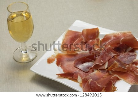 Dish of ham with a glass of wine - stock photo