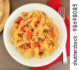 Dish of Italian pasta fusilli with fresh tomato sauce, capers and parmesan cheese - stock photo