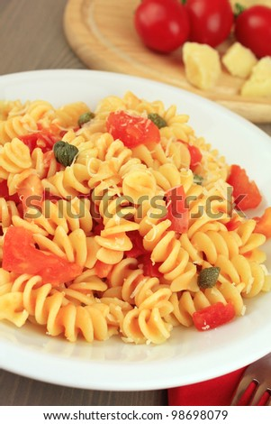 Dish of Italian pasta fusilli with fresh tomato sauce, capers and ...