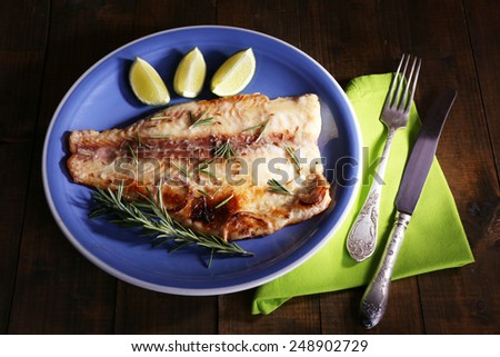 Dish of Pangasius fillet with rosemary and lime on wooden table background - stock photo