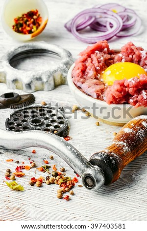 Dish of raw minced beef meat and parts of meat grinder - stock photo