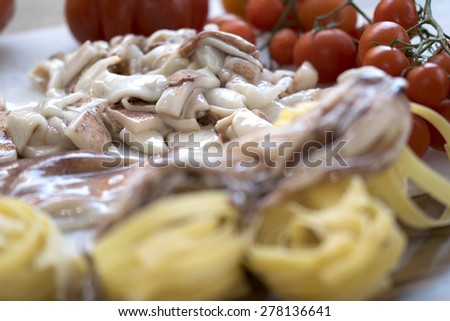 dish of sea with tagliatelle with squids anf fresh tomatoes - stock photo
