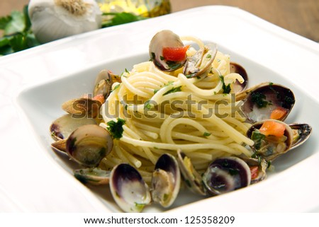 dish of spaghetti with clams on wooden table - stock photo
